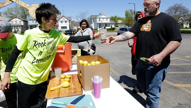 Jackson Goldapske of North Fond du Lac hands Dan Westphal of Fond du Lac a fresh-squeezed lemonade during a previous Lemonade Day event in Fond du Lac. This year's event was postponed and later canceled, due to the COVID-19 pandemic.