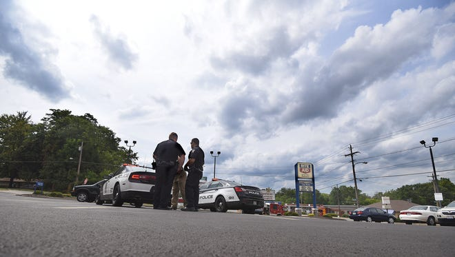 Mansfield police officers confer after working the scene of an overdose in the parking lot of Rite Aid on Park Avenue West and Trimble Road.