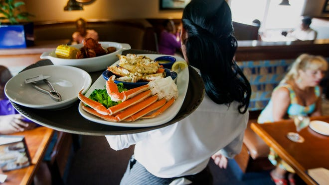 A waitress carries a tray a lobster kettle and a crab trio dish at a Red Lobster restaurant in Yonkers, New York.