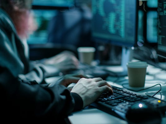 Close-up Shot of Hacker using Keyboard. There is Coffee Cups and Computer Monitors with Various Information.