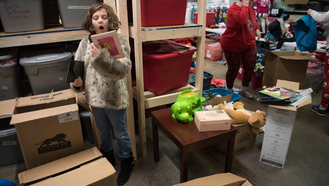 """Volunteer Emma Mattingly, 9, comes across a """"really cute"""" pink picture frame while sorting through donations at Borrowed Hearts at 1144 Indy Ct. in Evansville Thursday morning. Borrowed Hearts caters to foster parents who may need hygiene products, clothing or toys for their charges."""