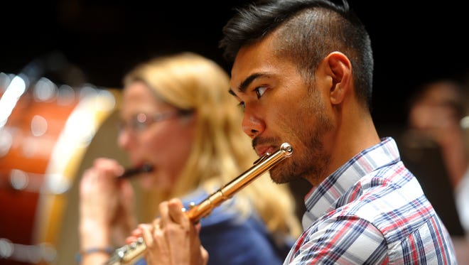 Flutist Norman Gonzalez rehearses with the Great Falls Symphony last month.