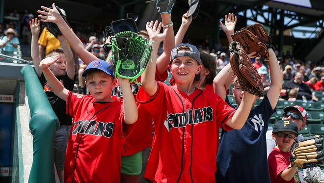 Kids stand near the Indians dugout between innings in hopes that a player will toss them a ball during a game between the Indianapolis Indians and the Columbus Clippers at Victory Field in Indianapolis, Sunday, July 8, 2018.