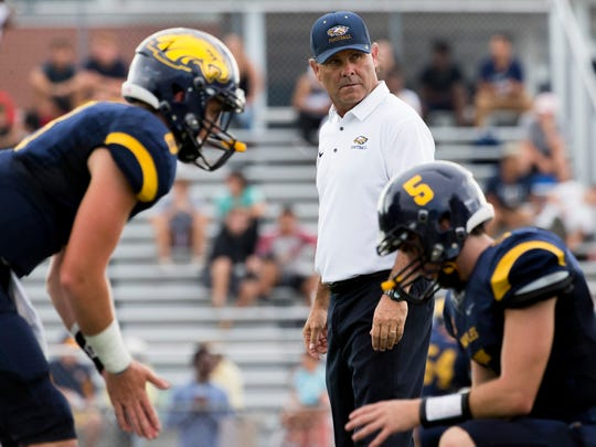 Naples High School football head coach Bill Kramer coaches his players during warmups prior to a preseason matchup with North Fort Myers at Naples High School Friday, August 18, 2017 in Naples.