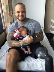 Chris Melendez sits with his son Vinny, who was born