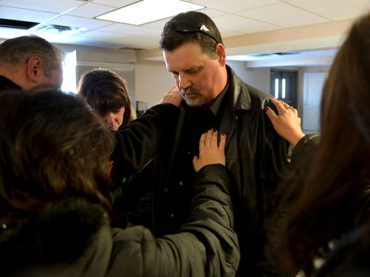 Members of the Household of Faith Church in Cottage Grove, Minn., pray for Michael Ball, center. Pastor Rich Pfeffer founded the church so people recovering from alcoholism or drug addiction can get help from God and from each other.
