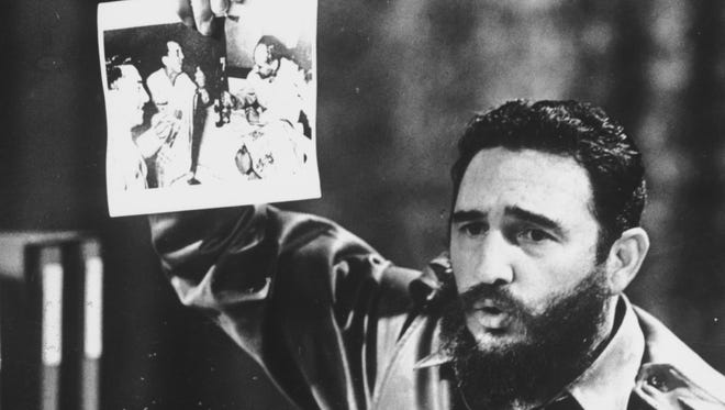 FILE - NOVEMBER 26, 2016: It has been reported that Cuba's former leader Fidel Castro has died at the age of 90. 5th July 1968:  Cuban Prime Minister Fidel Castro, presents a photograph in which General Ovando Candia and other men of the Bolivian Army get drunk to celebrate the murder of Che Guevara, the Latin American revolutionary.  (Photo by Keystone/Getty Images) ORG XMIT: 71088493 ORIG FILE ID: 3363226