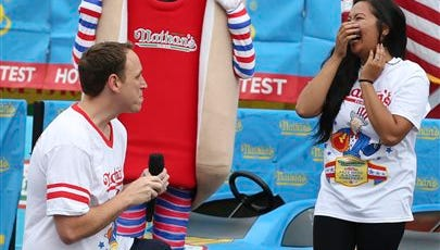 Competitive eater Joey Chestnut proposes to his girlfriend and fellow competitor Neslie Ricasa before the Nathan's Famous Fourth of July International Hot Dog Eating contest at Coney Island, Friday, July 4, 2014, in New York. Chestnut won his competition and eighth consecutive contest by finishing 61 hot dogs and buns.