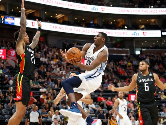 Grizzlies forward Jaren Jackson Jr. (13) goes to the basket as Hawks forward John Collins, left, and Omari Spellman (6) defend during the second half of an NBA Summer League game Monday.