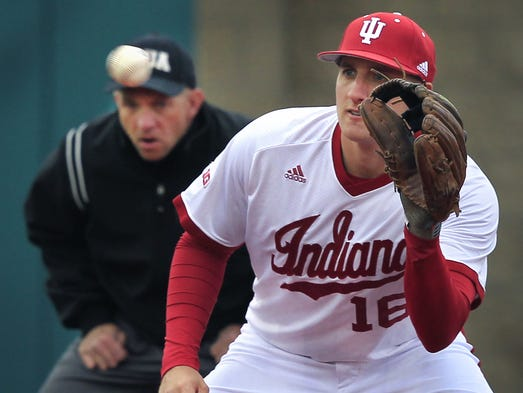 Indiana University third baseman Dustin DeMuth waits for the ball in the watchful eye of third base umpire Kyle George during action against the Louisville Cardinals at Bart Kaufman Field in Bloomington on Wednesday, March 19, 2014. The Hoosiers ended the Top 10-rated Cardinals' seven-game winning streak with a 9-3 win.