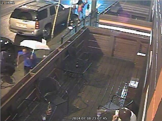 Police say the man with the umbrella is a suspect in a shooting outside the WKND Lounge.