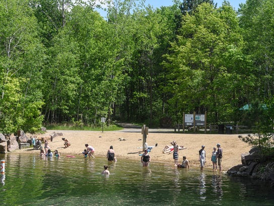 Swimmers enjoy the sandy beach at Quarry 11 Friday,