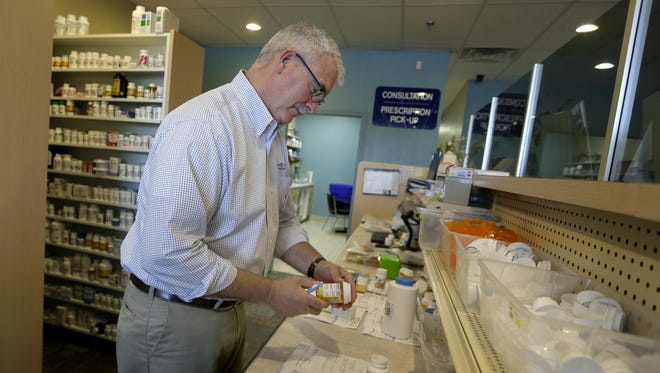 Pharmacist and co-owner Jeff Cushman fills prescriptions Wednesday at Hometown Pharmacy in Neenah.