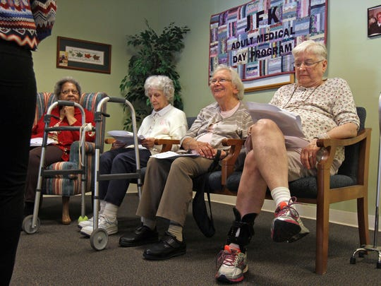 """JFK Adult Medical Day Program activity coordinator Gloria Lopez leads a memory program at the Edison center. They were using the book """"Mothballs in My Attic"""" to facilitate."""