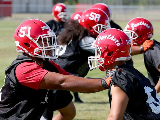 Central Panthers lineman Marlon Tuipulotu, left, goes through a drill during practice, Monday, August 17, 2015, in Independence, Ore.