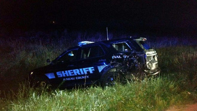 A Juneau County squad car sits in the ditch along State 12, near Mauston Saturday after being hit by a suspected drunken driver.