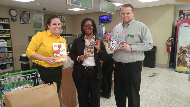 Publix employees at the Martin Downs, Palm City store Britney Aten, left, Marvette Grey and Shawn Hawk show some of the books collected for Caring Children Clothing Children.