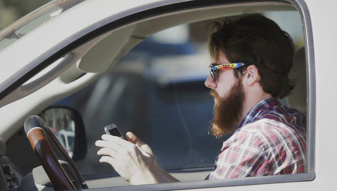 An man works his phone as he drives through traffic in Dallas. Tuesday the National Highway Traffic Safety Administration issued voluntary guidelines aimed at manufacturers of smart phone and tablet. The goal is to ban drivers from using distracting apps while the vehicle is in motion.