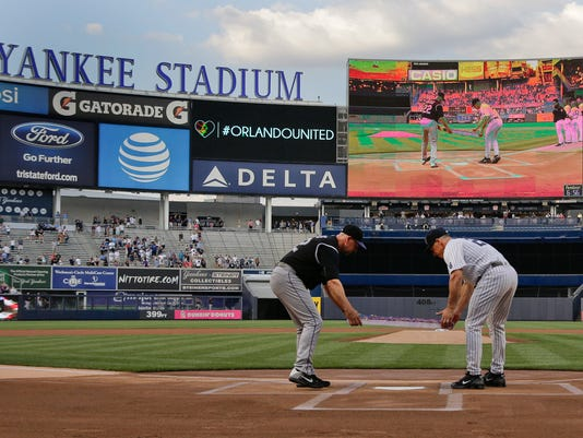 Colorado Rockies manager Walt Weiss, left, and New York Yankees manager Joe Girardi lay a rainbow-colored wreath across home plate during a ceremony remembering the victims of the Orlando shootings, before a baseball game Tuesday, June 21, 2016, in New York. (AP Photo/Julie Jacobson)