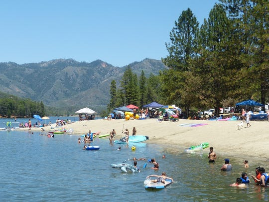 People pack Whiskeytown National Recreation Area's Brandy Creek Beach last July. Park officials say Brandy Creek beach visitors need to arrive early on the Fourth of July so they don't have to wait in a line of cars for a parking spot.