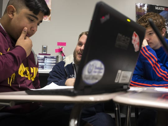 Jason Redd (center) works with Angel Meza (left) and Christian Graziano in a geometry class at Dobson High School in Mesa on Nov. 20, 2017.