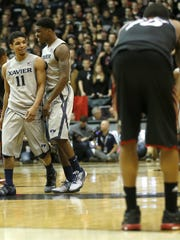 Xavier Musketeers players celebrate their 59-57 win