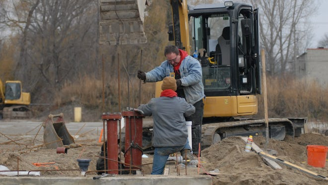 Crew members work near the planned site for an 83-room Holiday Inn Express at the Water Street Marina on Tuesday.