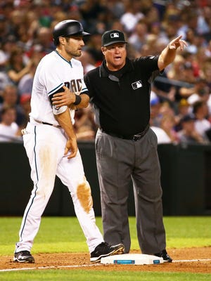 Third base umpire Marvin Hudson sends Arizona Diamondbacks A.J. Pollock back to second after a throwing error by Colorado Rockies pitcher Adam Ottavino in the 7th inning on Friday, April. 28, 2017 at Chase Field in Phoenix, Ariz.