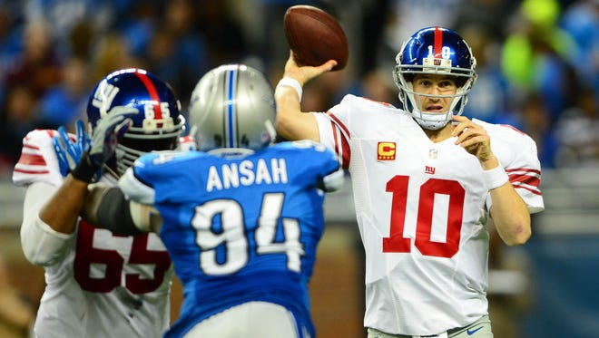 New York Giants quarterback Eli Manning (10) throws a pass while being pressured by Detroit Lions defensive end Ezekiel Ansah (94) during the third quarter at Ford Field.