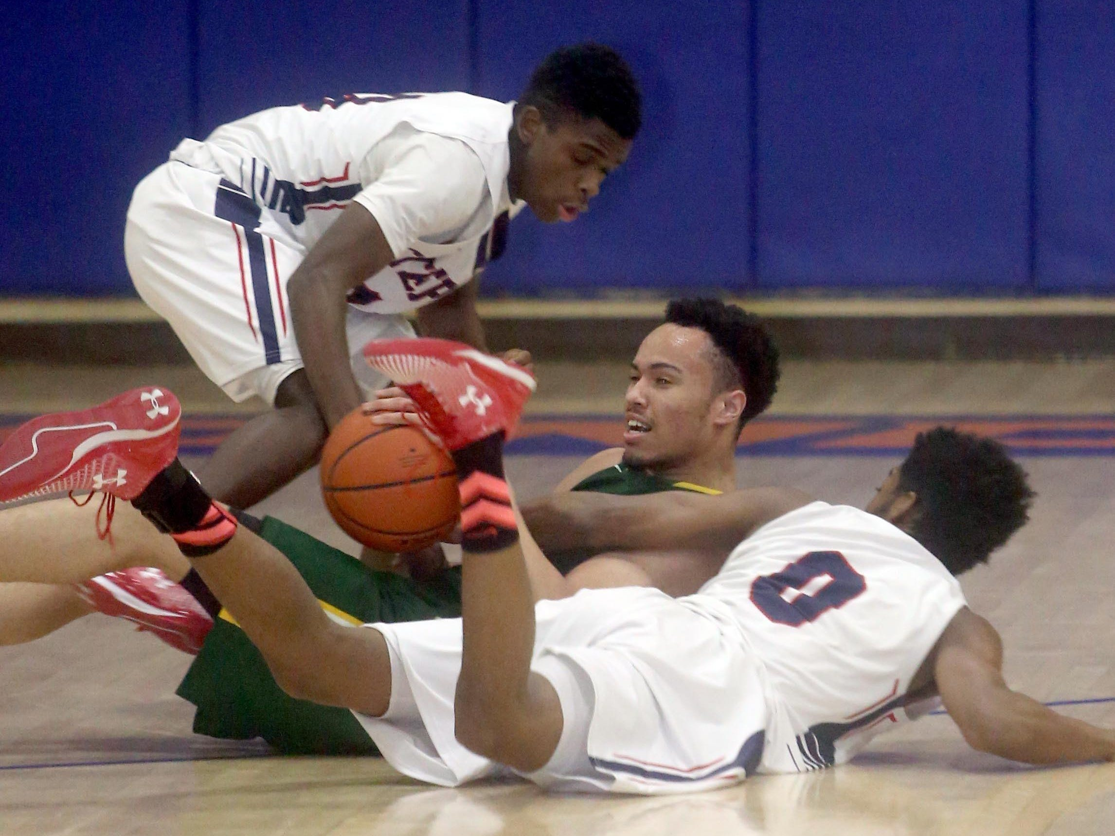 Stepinac's Makai Johnson and Jordan Means battle Yannic Williams of Holy Cross during a CHSAA second round AA playoff basketball game against St. Peter's at St. Raymond High School in the Bronx March 3, 2016.