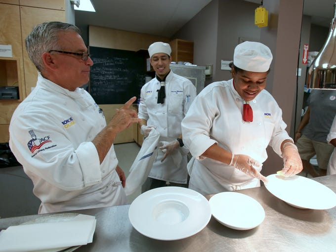 Chef Michael Vignapiano works with students Hector Mendez of Yonkers and Tanisha Myrie of New York City in Monroe College's culinary arts program at the student-run restaurant, the Dining Lab in New Rochelle Sept. 24, 2014.