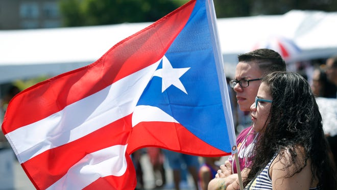 Zack and Shayneska Millspaugh of Hamlin, took a flag with them to the 48th Annual Puerto Rican festival at the Frontier Field VIP Parking Lot.