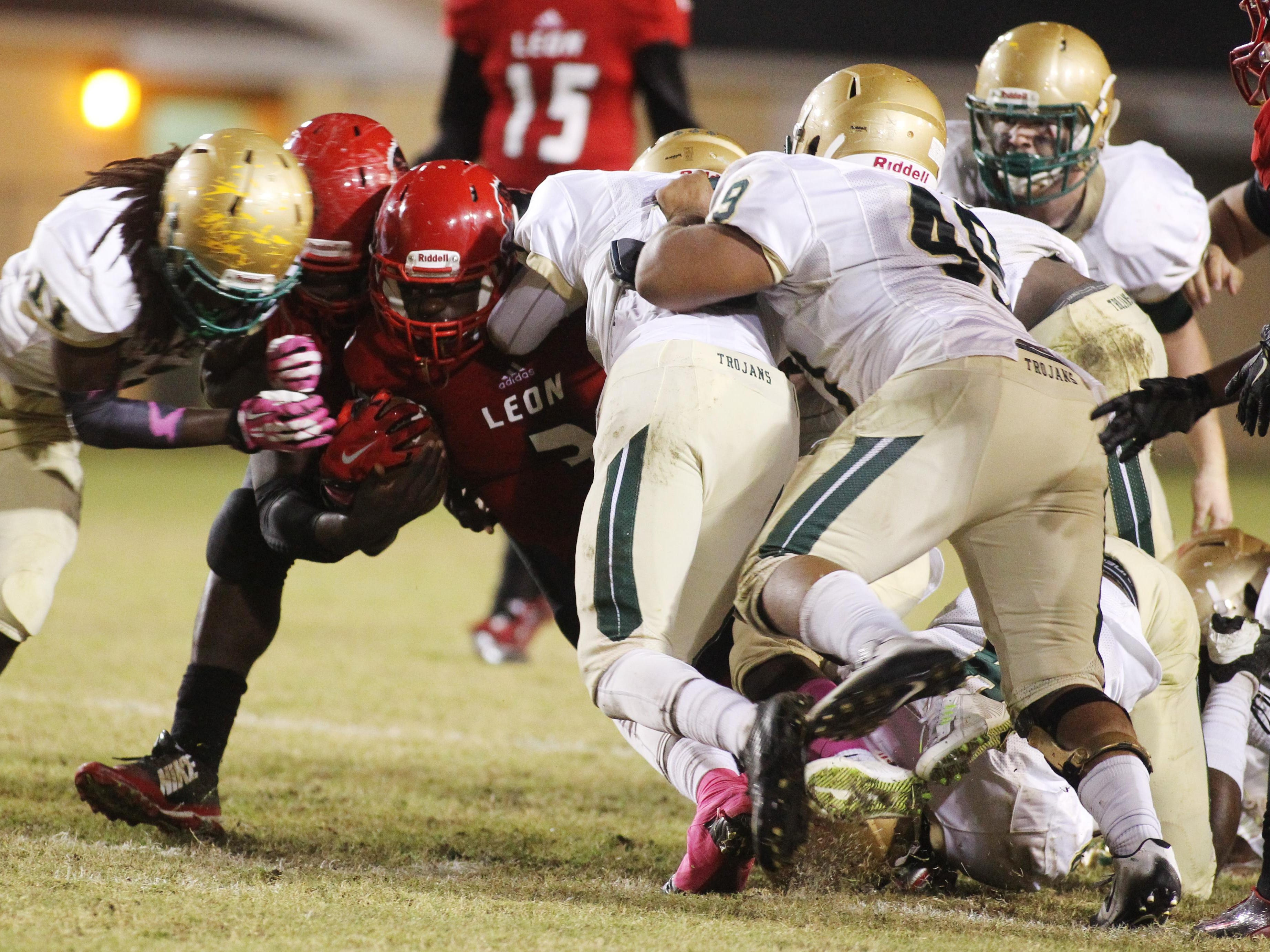 Leon High wide receiver J'air Jones tries to run through a wall of Lincoln High defenders in Friday's game at Cox Stadium.