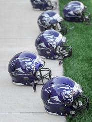 ACU helmets sit on the sideline while the team works