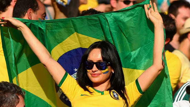 A Brazil fan waves a Brazil flag in the grandstands prior to the game against Croatia in the opening game of the 2014 World Cup at Arena Corinthians.