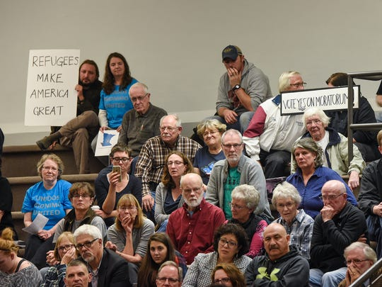 Audience members hold signs during a St. Cloud city council meeting on proposed moratoriums on refugee resettlement Monday, Oct. 23, in St. Cloud.