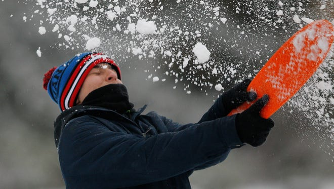 Kennesaw University student Thomas Grey swings at a snowball as snow falls, Feb. 25, 2015, in Kennesaw, Ga.