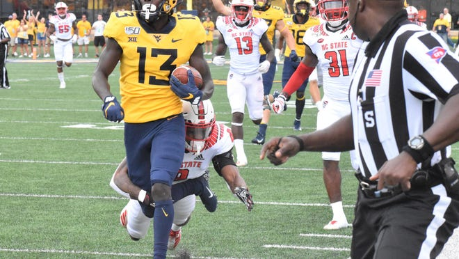 Sam James (13) of Richmond Hill scores a touchdown for West Virginia against North Carolina State last season.