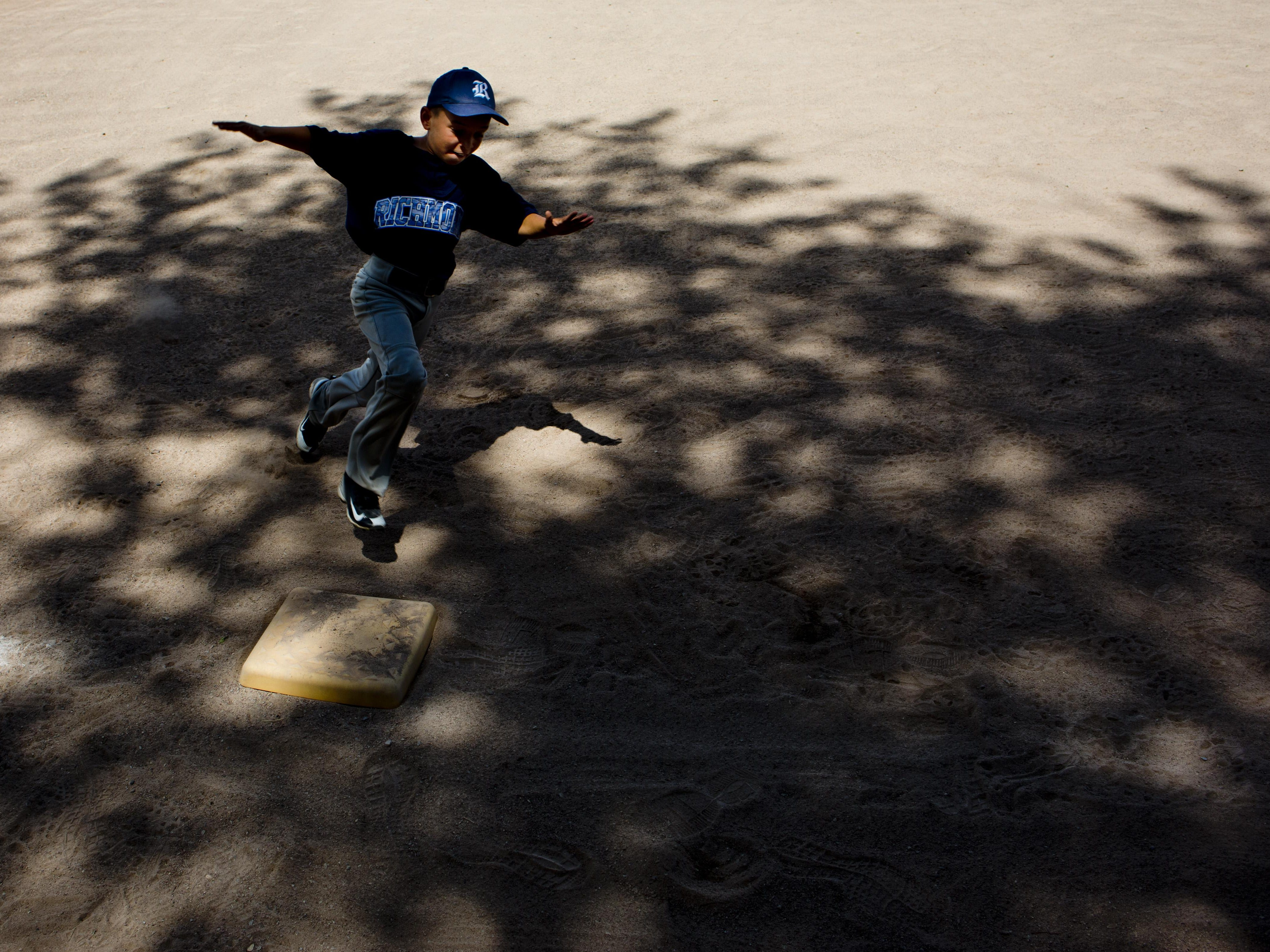 Richmond's Maximus Greenia, 9, rounds third while competing in base running during a Little League skills competition Saturday, August 1, 2015 at Marysville City Park.