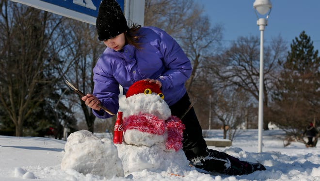 Maria Macey, 14, of Marysville, builds a snowman Saturday at Lincoln Park in Port Huron.