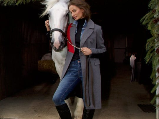 A woman poses with a horse.
