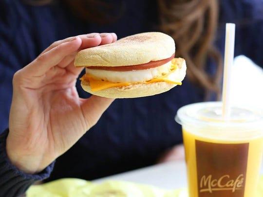 A customer holds a McDonald's breakfast sandwich.