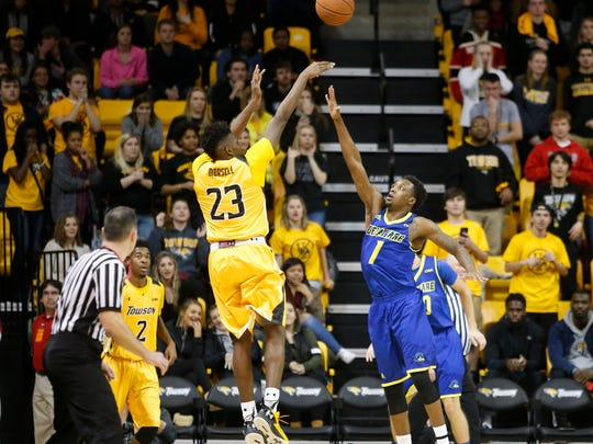 Towson's Mike Morsell shoots a three-pointer over Delaware's Kory Holden, good for a 94-91 lead with 37 seconds remaining in overtime in Delaware's 101-97 loss at Towson University Saturday.