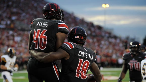 UofL's Lamar Atkins (left) and Gerald Christian (right) celebrate Christian's touchdown against Murray State on Saturday at Papa John's Cardinal Stadium. (By David Lee Hartlage, Special to the C-J) Sept. 6, 2014.