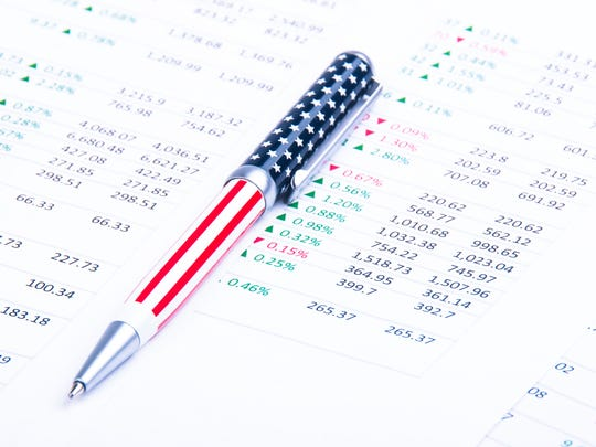 An American flag-themed pen lying atop a printout of financial data.