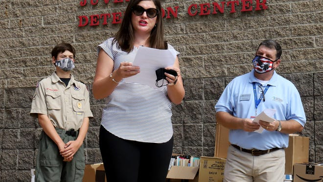 Eagle Scout Candidate Aaron Millard, left, and Leadership Fort Smith's Mark Allen look on during a press conference at the Sebastian County Juvenile Detention Center, as LFS member, Heather Ketter, thanks LFS alumni and community for their donations to the 2020 LFS class project that will benefit the Sebastian County JDC with 800 books and puzzles as well as $1,625 to the United Way of Fort Smith Dolly Parton Imagination Library. Boy Scout Troop 380's Millard, Scout Master David Higginbotham and Chris Millard built new book shelves for the additional resources and educational material stored in the SCJDC library.