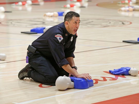 Milwaukee Fire Department Captain Leon Butts runs through instructions on administering chest compressions during a CPR training session.