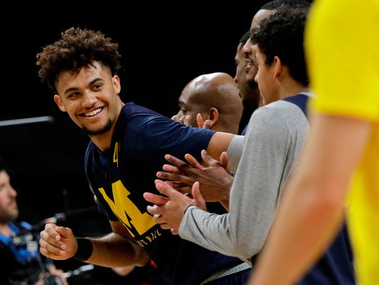 Michigan's Isaiah Livers (4) smiles as he works out with his teammates during a practice session for the Final Four NCAA college basketball tournament, Friday, March 30, 2018, in San Antonio. (AP Photo/David J. Phillip)