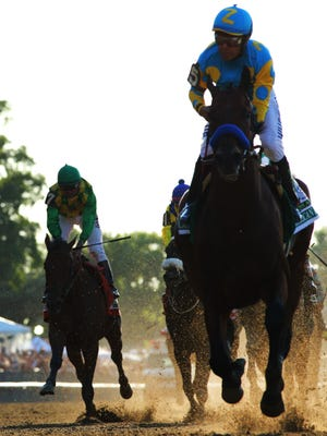 Victor Espinoza aboard American Pharoah (5) goes on to win the 2015 Belmont Stakes as Kent Desormeaux aboard Keen Ice (7) comes in third on the outside at Belmont Park.