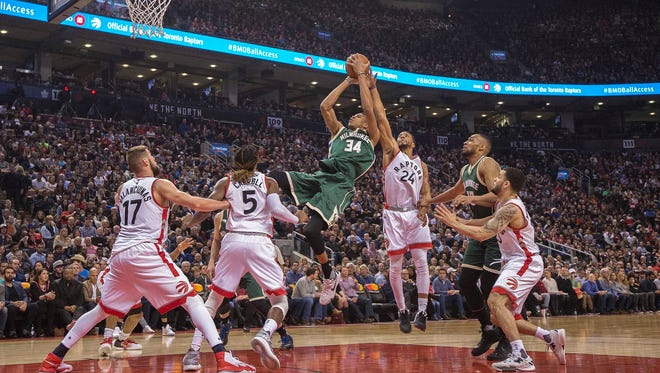 Bucks forward Giannis Antetokounmpo  takes a shot at the basket as Raptors guard Norman Powell tries to defend during the second quarter pg a game at Air Canada Centre.